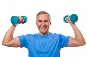 A senior man holding two dumbbells while flexing his muscles.