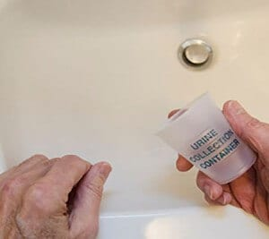 man leaning on sink with urine collection container